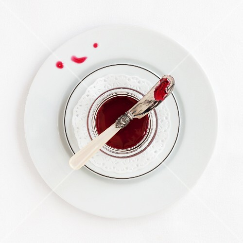 A dish of hibiscus syrup with a knife