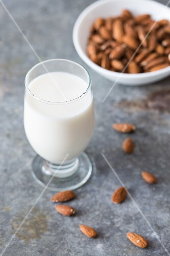 A glass of almond milk and a bowl of whole almonds