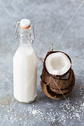 Coconut milk in a bottle with a fresh coconut