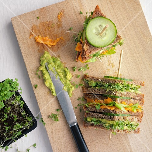 Triangular sandwiches on a sticks with carrots, cucumber, avocado and tahini