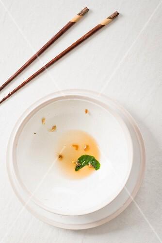 An oriental arrangement featuring an empty soup bowl and chopsticks