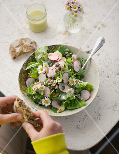 Leaf salad with radishes, daisies and crispy seed mix