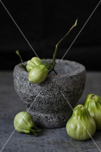 Green tomatoes in a mortar