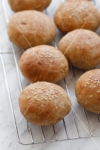 Wholemeal rolls with sesame seeds on a wire rack