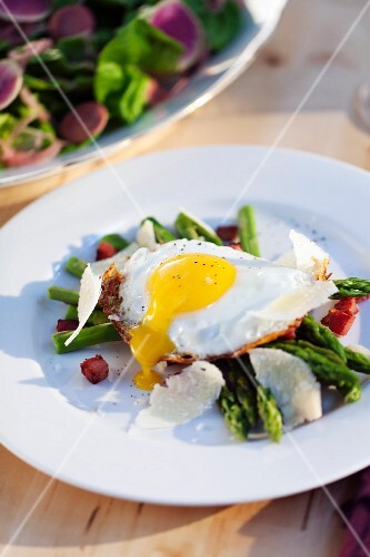 Fried egg on green asparagus with diced bacon and Parmesan cheese