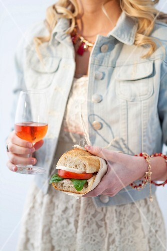 A young woman with a tomato and mozzarella sandwich and an Aperol Spritz