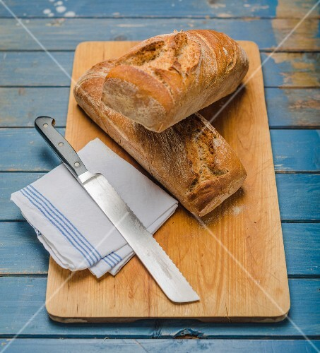 Sour dough bread on a chopping board with a knife