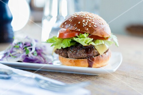 A hamburger with cheese, lettuce and tomato served with coleslaw