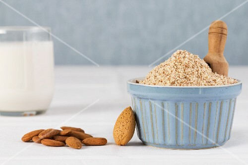 A glass of almond milk with whole and grated almonds