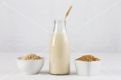 A bottle of oat milk with two dishes of oats and oatmeal