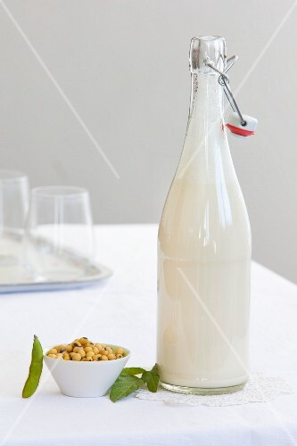 A bottle of soya milk and a dish of soya beans