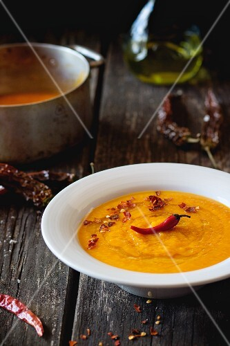 Cream of carrot soup with chilli peppers on a wooden table