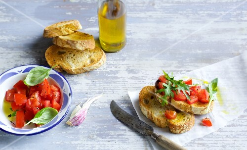 An arrangement of tomatoes, grilled bread, olive oil and bruschetta