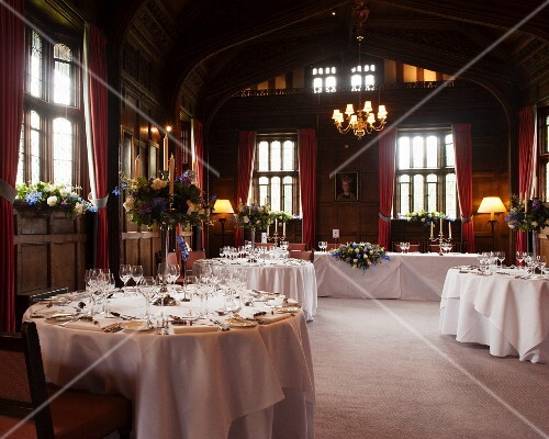 Tables festively set for wedding in interior of Hever Castle, Kent, England