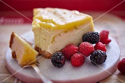 A slice of cheesecake with a fruit glaze and red berries