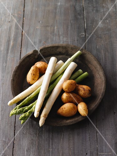 White and green asparagus with potatoes in a wooden bowl