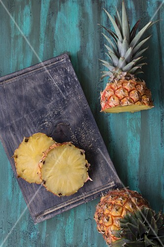 A pineapple, whole, halved and sliced (seen from above)