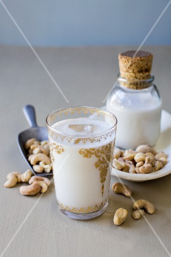 Cashew milk in gold-embossed glass with scattered cashew nuts