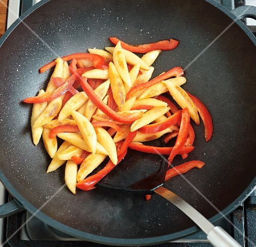 Potato orzo pasta and pepper strips being fried in a wok