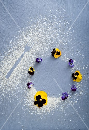 A fork print in icing sugar and round biscuits decorated with pansies