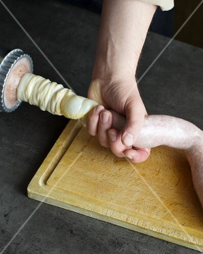 An intestine being filled with sausage meat