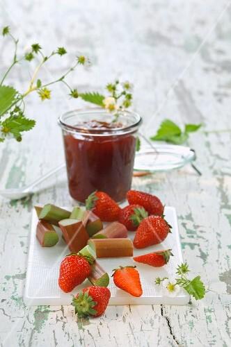 A jar of strawberry and rhubarb jam, fresh strawberries and rhubarb on a chopping board