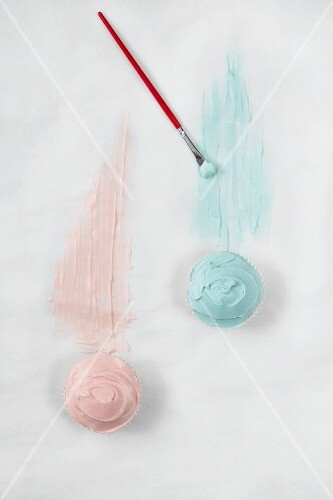 Two cupcakes with pink and blue frosting and a brush