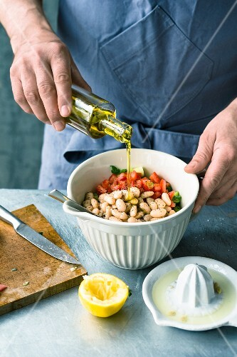 White beans and vegetables being marinated in olive oil