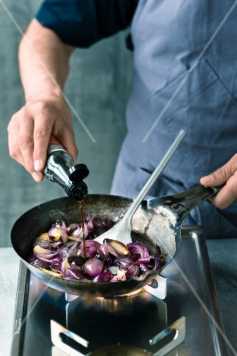Steamed red onions being quenched with soy sauce
