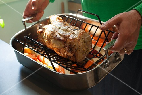 Roast pork and vegetables in a roasting tin