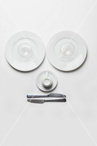 A face made up of plates, glasses, a cup and knives