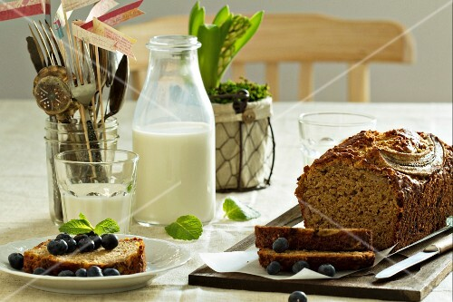 Banana bread, sliced, with blueberries and milk