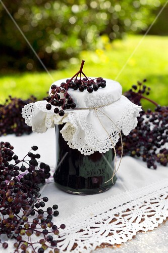 A jar of homemade elderberry jelly with a decorative lived and a sprig of ripe elderberries on a garden table