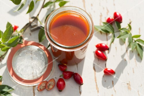 Homemade rose hip jelly in an open jar on a garden table