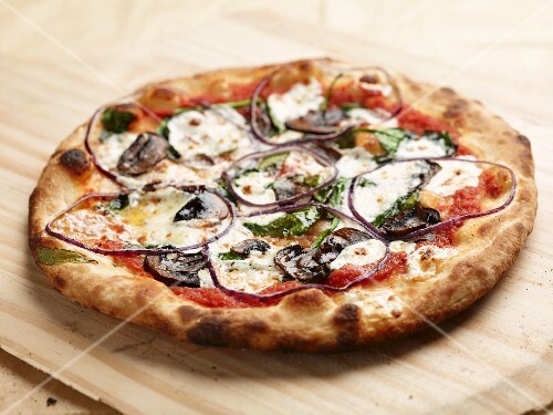 Mushroom, spinach and mozzarella pizza baked in a wood-fired oven