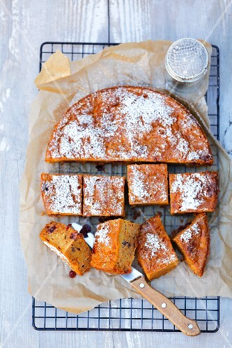 Pumpkin cake with cranberries and icing sugar (seen from above)