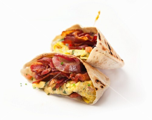 Pita bread filled with scrambled eggs and bacon on white surface