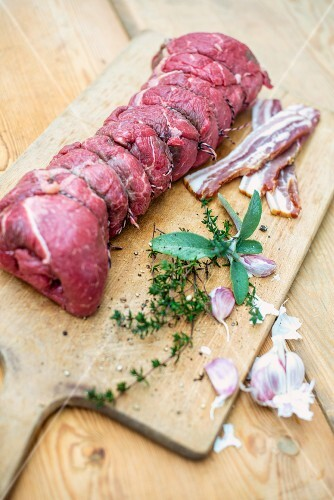 Ready-to-cook beef roulade with ingredients on a wooden chopping board