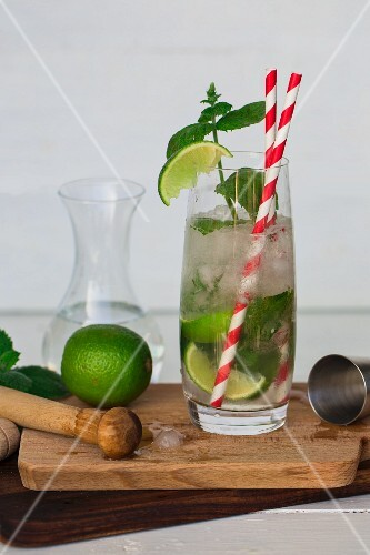 A mojito with limes, mint and straws