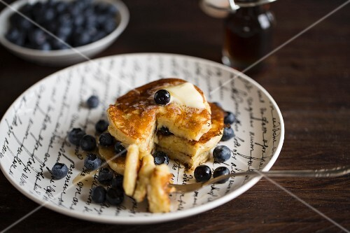 Banana pancakes with blueberries and maple syrup
