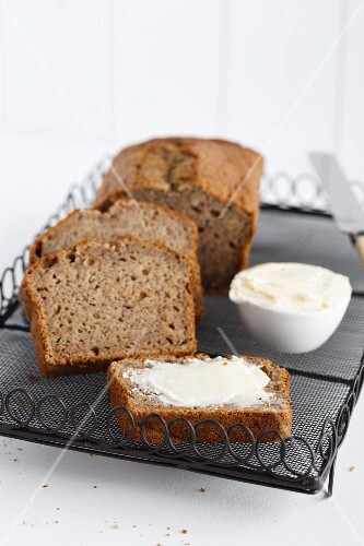 Freshly baked banana bread, sliced, with butter on a cooling rack