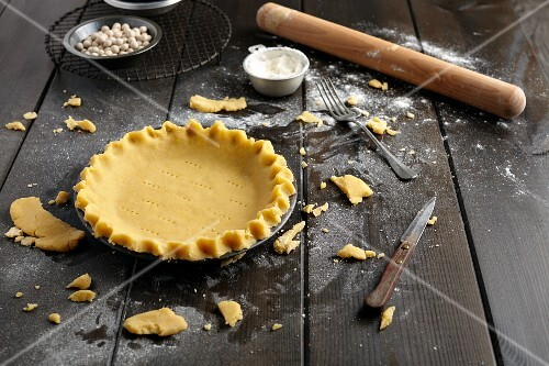 Shortcrust pastry dough, pricked with a fork in a baking tin
