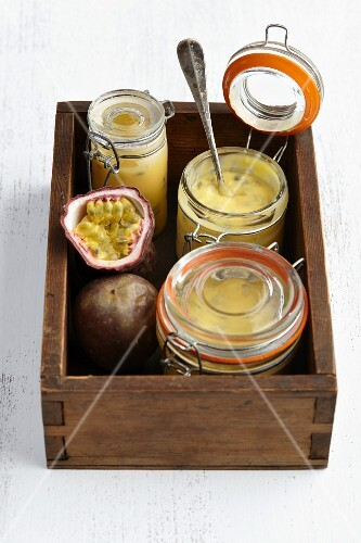 Preserving jars with passion fruit spread in a wooden crate