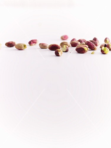 Pistachio nuts on a white surface