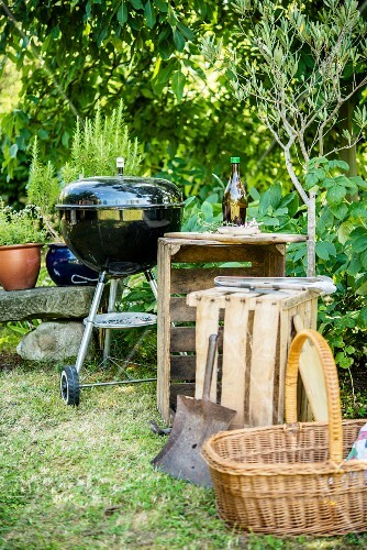 A wooden charcoal grill, wooden boxes and a basket in a garden