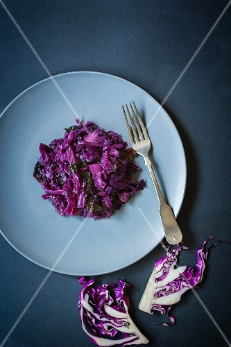 Red cabbage on a plate with a fork next to raw red cabbage