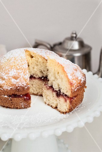 A mini Victoria sponge cake on a white cake stand with a teapot in the background
