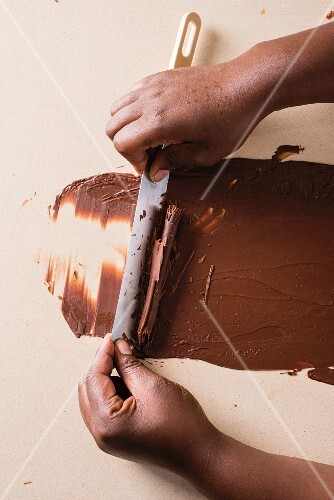 Chocolate rolls being scraped with a knife