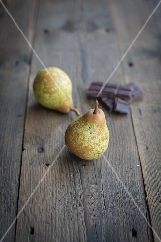 Two pears and pieces of chocolate on a wooden surface