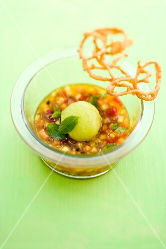 Summer fruit minestrone with basil and melon sorbet and a crispy vanilla lattice served in a glass